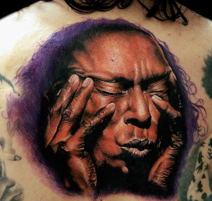 Realism style colored back tattoo of ancient man face