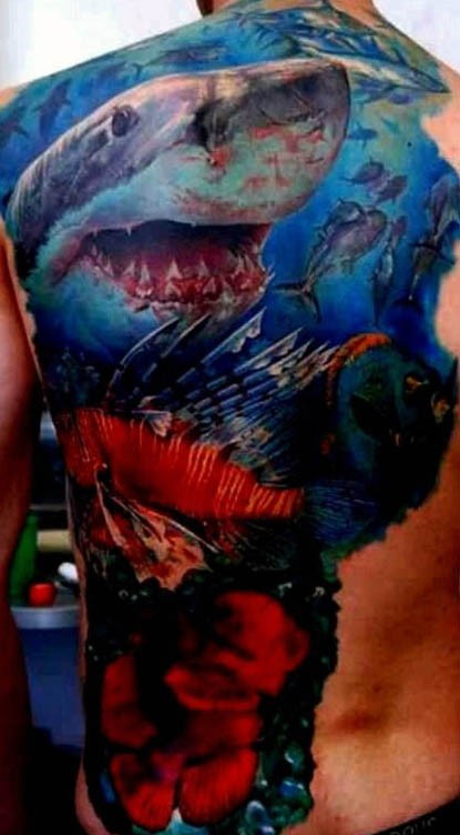 Realism style colored back tattoo of bloody shark and fishes