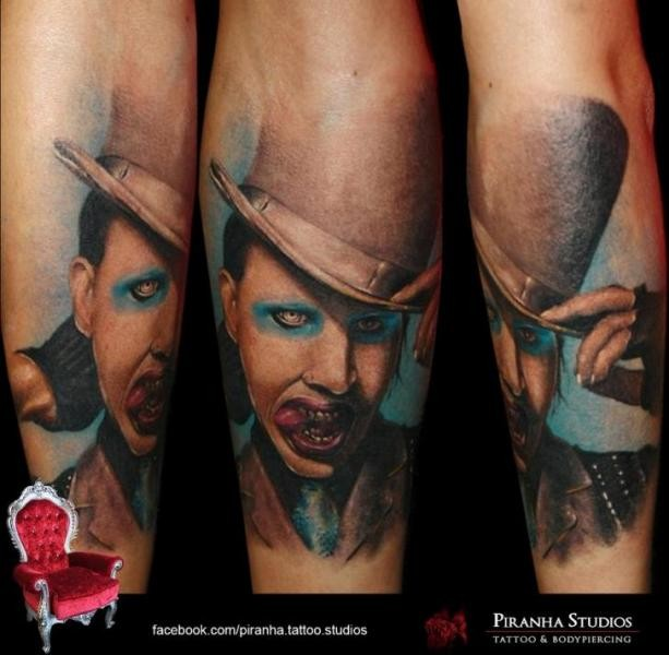 Realism style colored forearm tattoo of Merlin Manson in hat