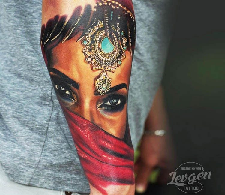 Realism style colored forearm tattoo of Eastern woman face stylized with beautiful jewelry