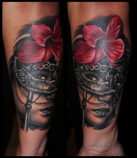 Realism style colored forearm tattoo of woman with mask and flower