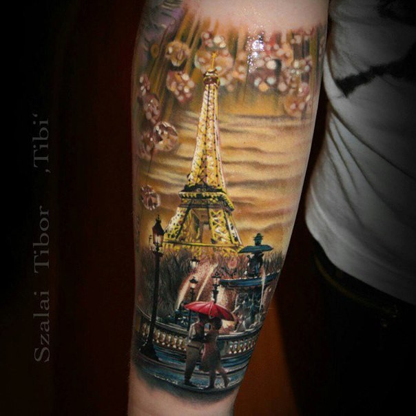 Realism style colored forearm tattoo of night Paris with kissing couple and Eiffel tower