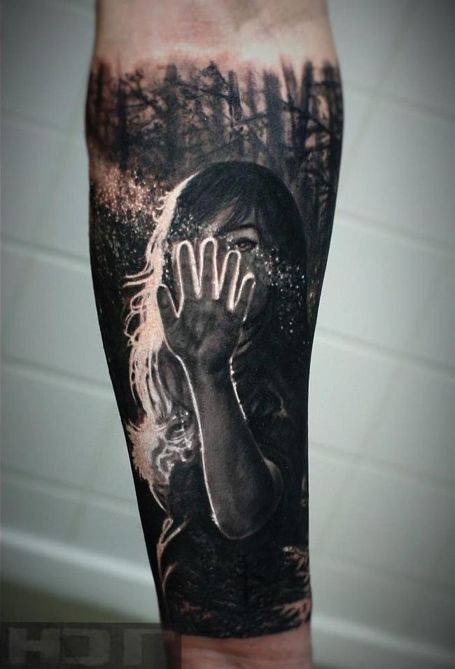 Realism style colored forearm tattoo of woman with sun light in dark forest