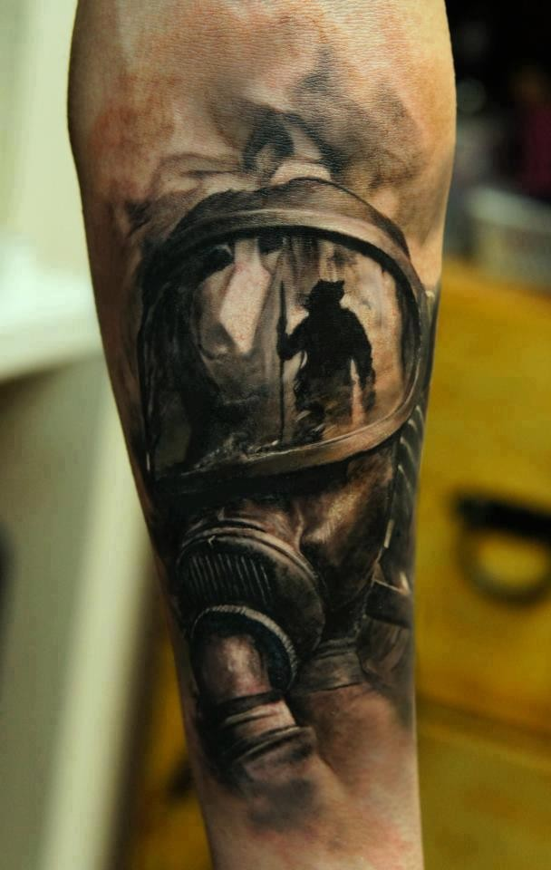 Realism style colored forearm tattoo of man in gas mask