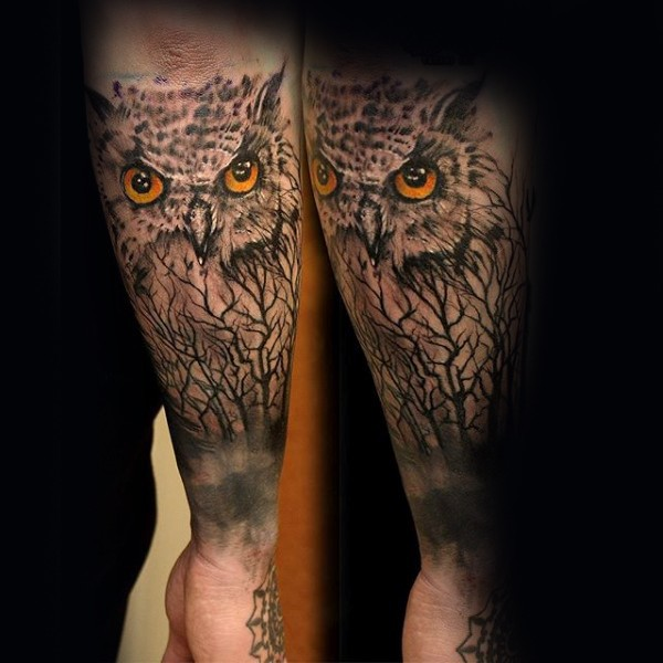 Realism style colored forearm tattoo of owl with trees