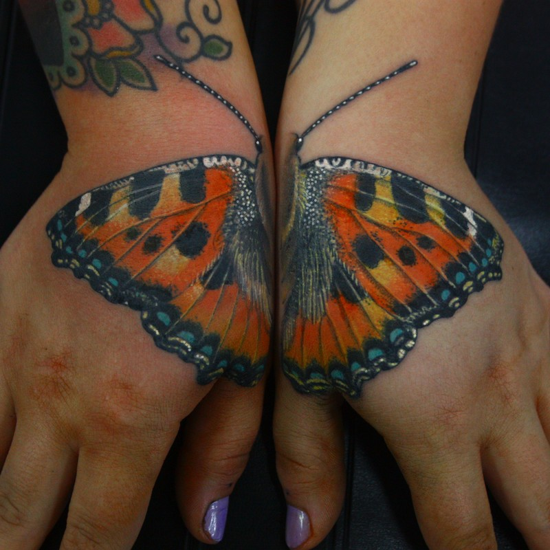Realism style colored hands tattoo of beautiful butterfly