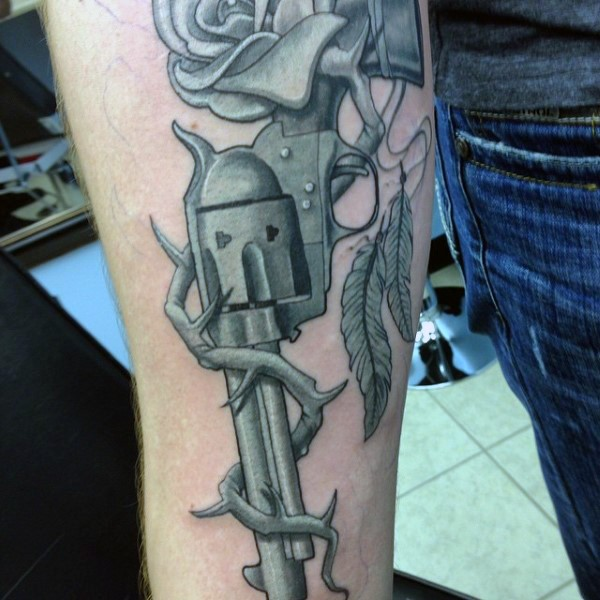 Realism style colored revolver tattoo on forearm with rose vine