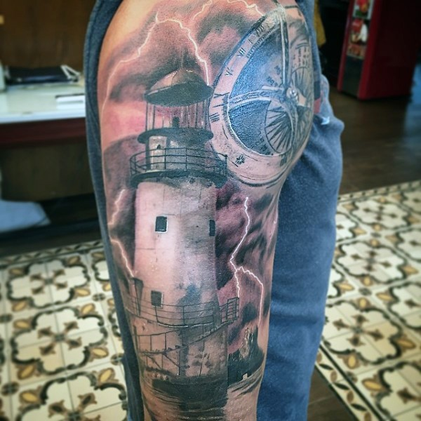 Realism style colored shoulder tattoo of light house with lightning and compass