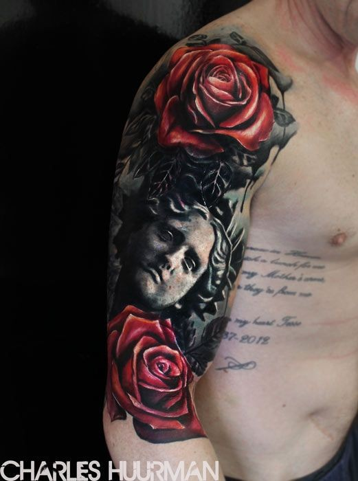 Realism style colored shoulder tattoo of statue with roses