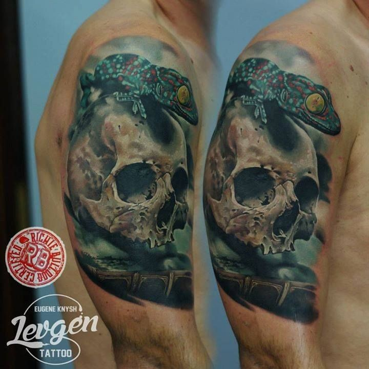 Realism style colored shoulder tattoo of human skull and lizard