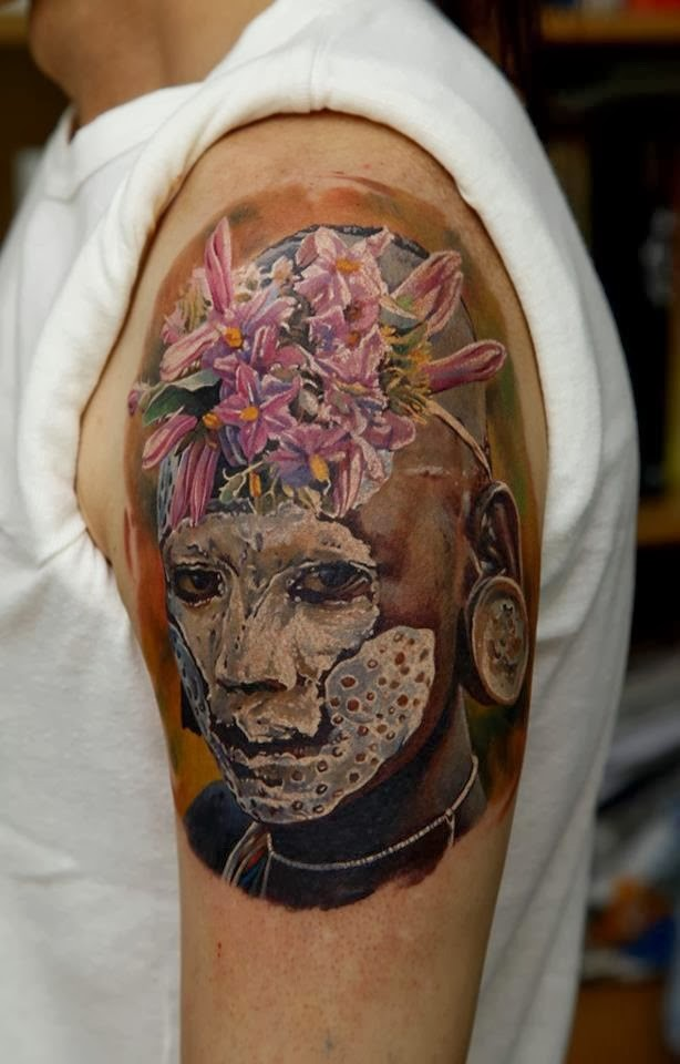 Realism style colored shoulder tattoo of tribe man portrait with flowers