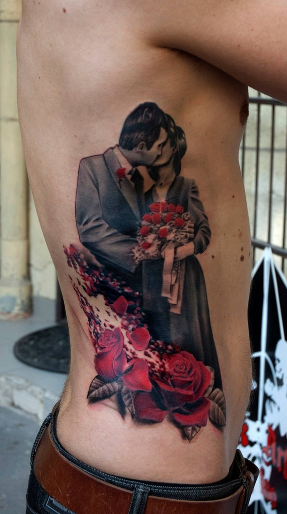 Realism style colored side tattoo of kissing couple with flowers