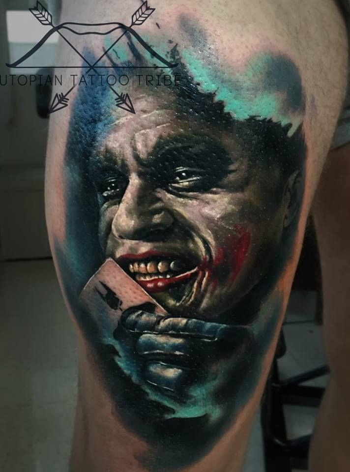 Realism style colored thigh tattoo of evil Joker face