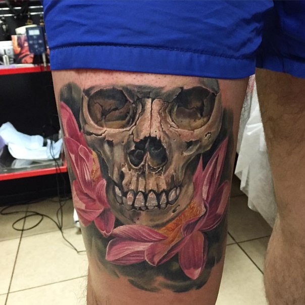 Realism style colored thigh tattoo of human skull with beautiful flowers