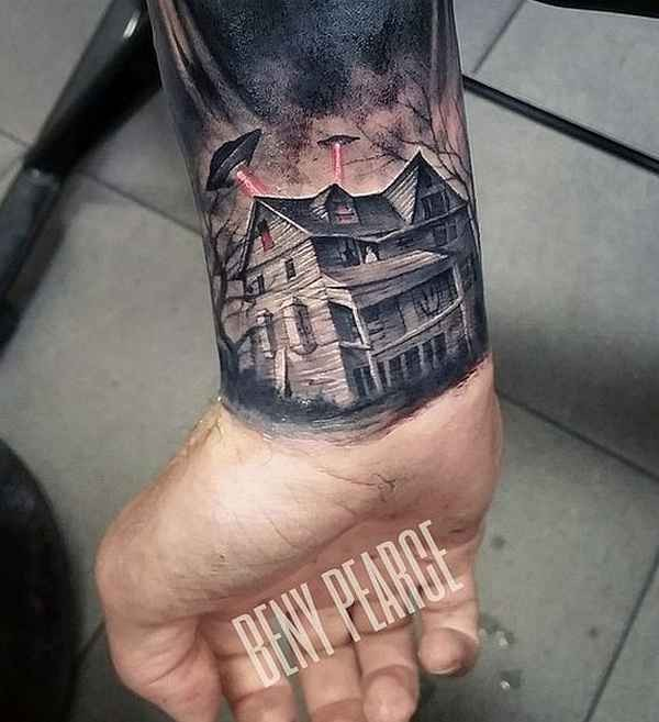 Realism style colored wrist tattoo of alien ships and abandoned house