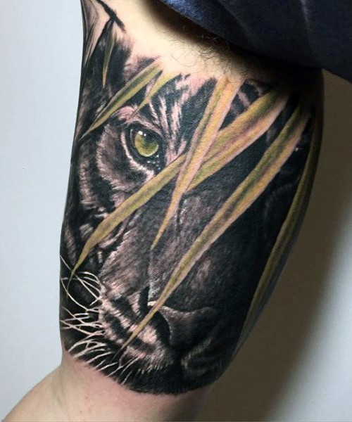 Realism style cool looking biceps tattoo of tiger in jungle