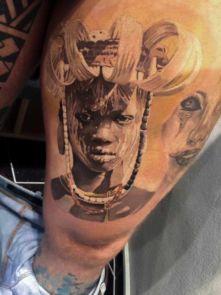 Realism style detailed thigh tattoo of tribal human portrait