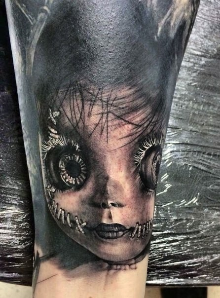 Realism style very detailed arm tattoo of creepy doll face