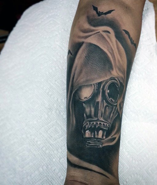 Realism style very detailed gas mask under hood tattoo on forearm stylized with bats
