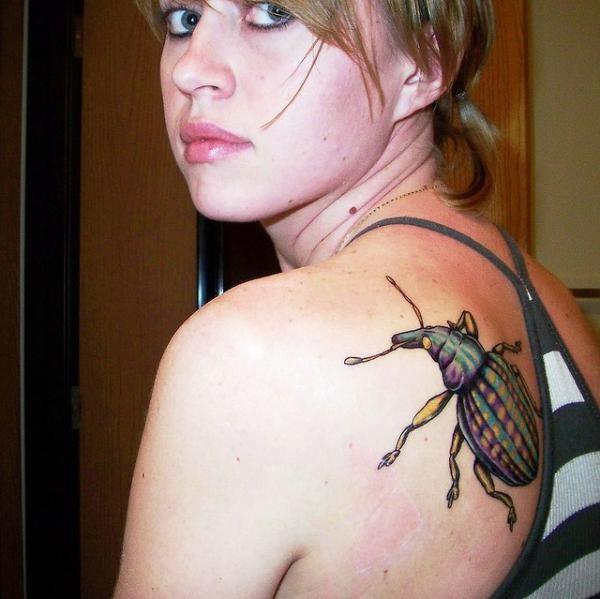Realistic bug tattoo on shoulder blade
