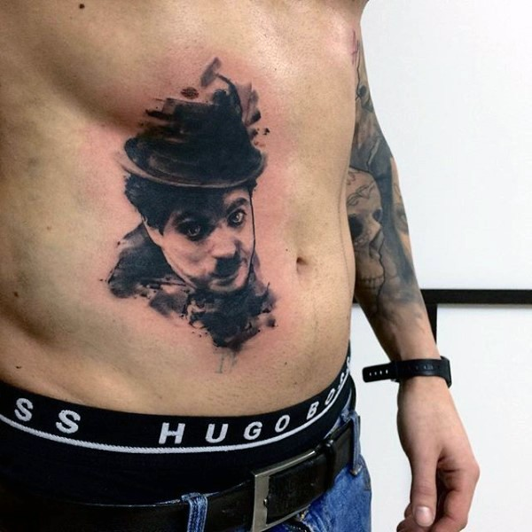 Realistic Charlie Chaplin portrait tattoo on belly with paint drips