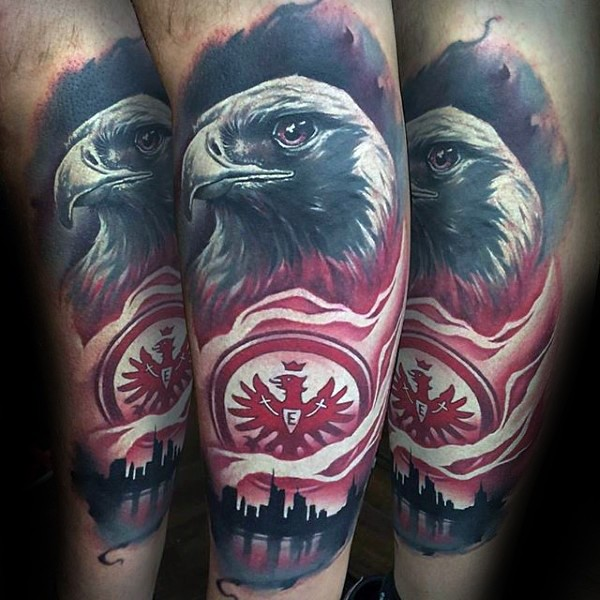 Realistic looking arm tattoo of eagle with city sights and emblem