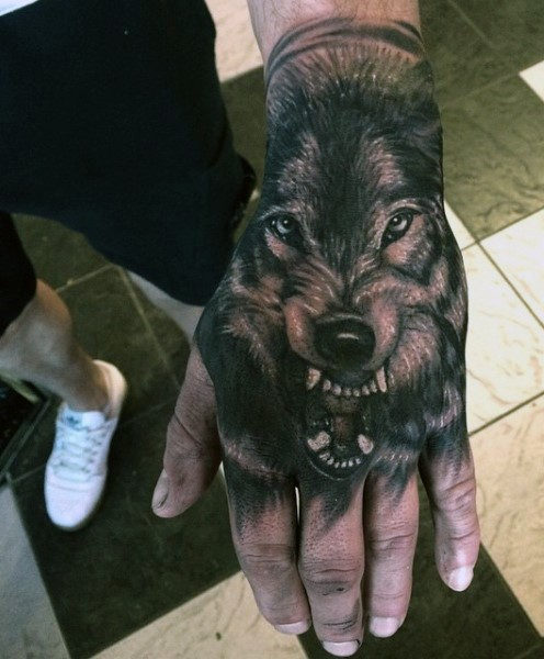 Realistic looking black and white hand tattoo fo roaring wolf head