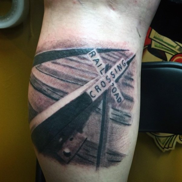 Realistic looking black and white rail road with sign tattoo on arm
