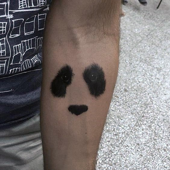 Realistic looking black ink forearm tattoo of panda bear face