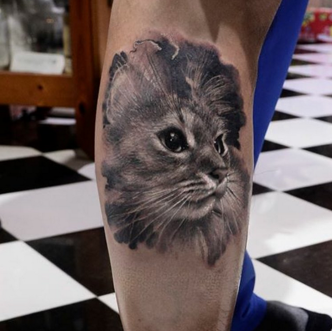 Realistic looking black ink leg tattoo of cute cat portrait