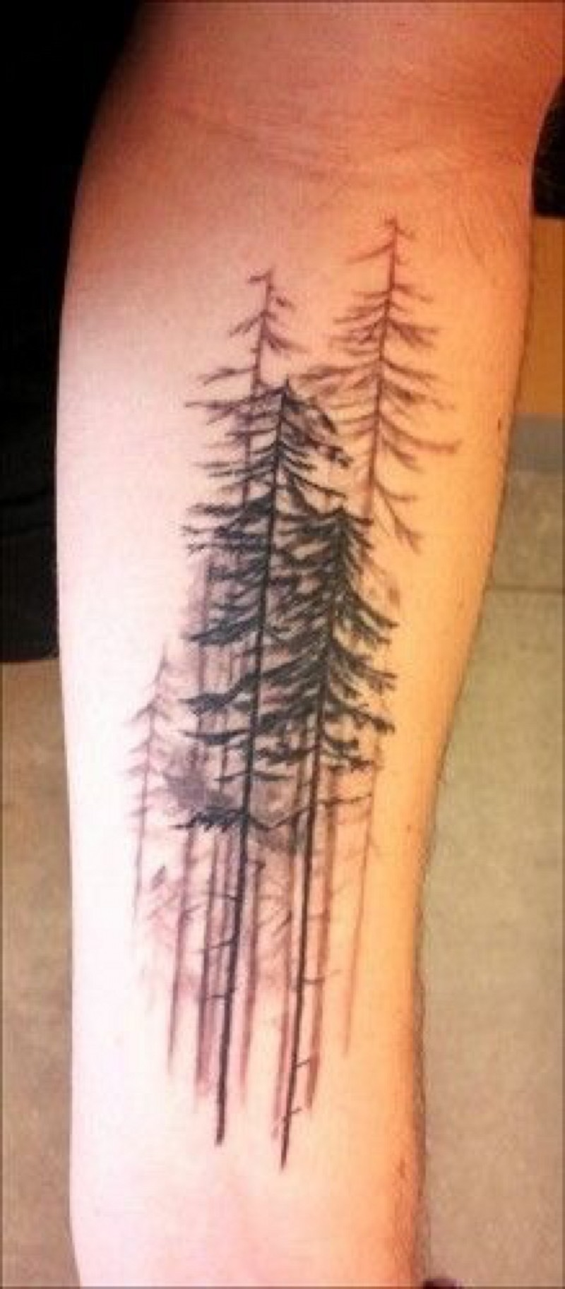 Realistic looking black ink old forest tattoo on arm