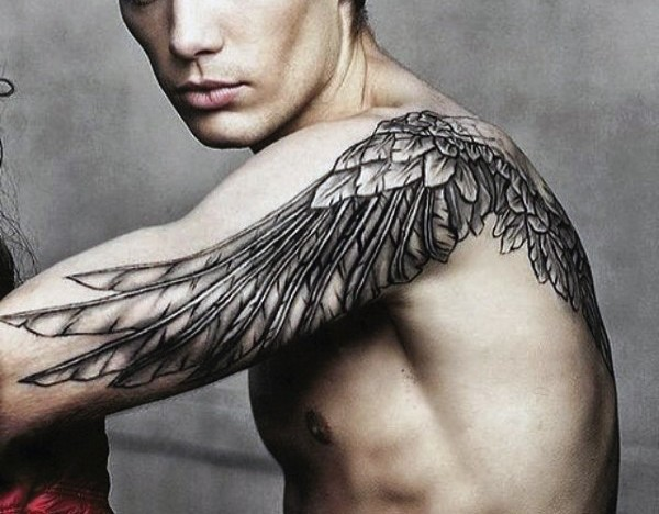 Realistic looking black ink wing tattoo on shoulder