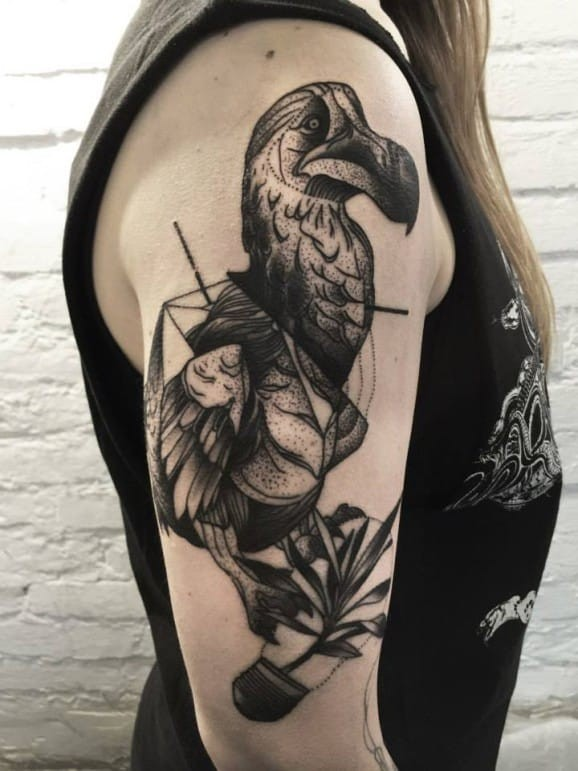 Realistic looking blackwork style upper arm tattoo of large bird with leaves by Michele Zingales