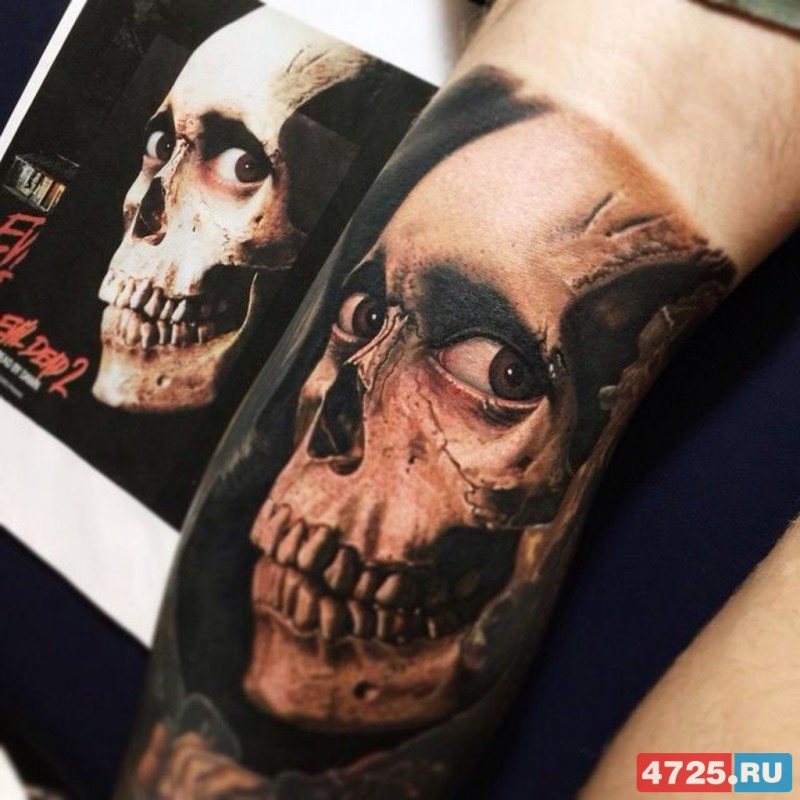 Realistic looking colored arm tattoo of creepy human skull with eyes