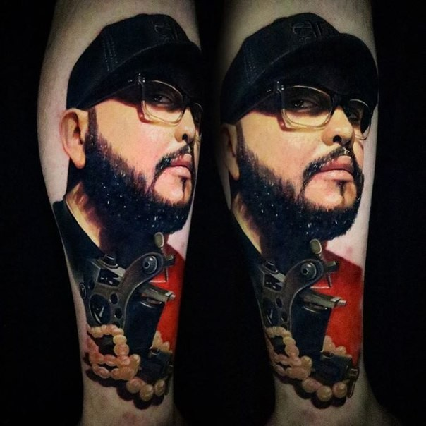 Realistic looking colored arm tattoo of man face with tattoo machine