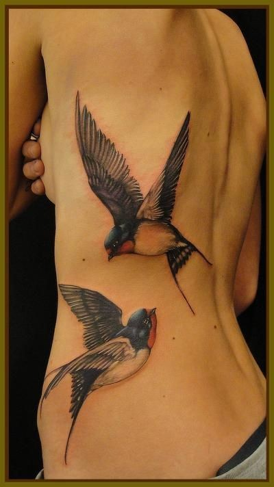 Realistic looking colored flying big birds tattoo on back