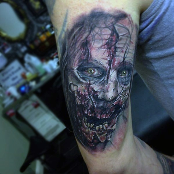Realistic looking colored horror style arm tattoo of zombie face