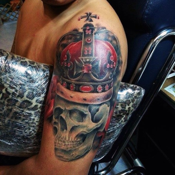 Realistic looking colored shoulder tattoo of skull with crown