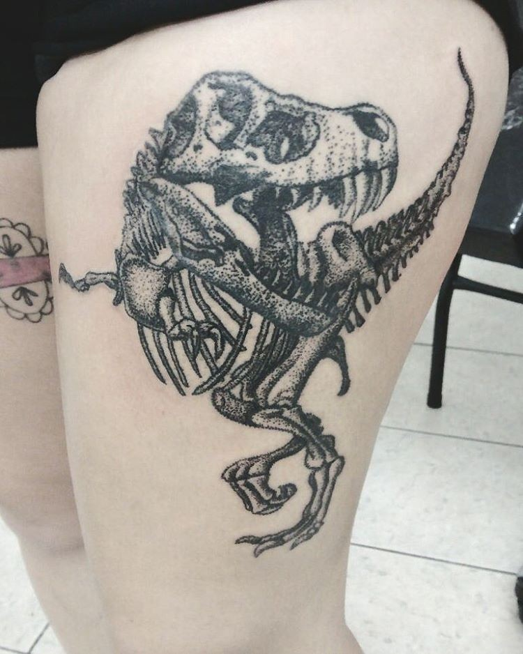 Realistic looking engraving style thigh tattoo of dinosaur skeleton