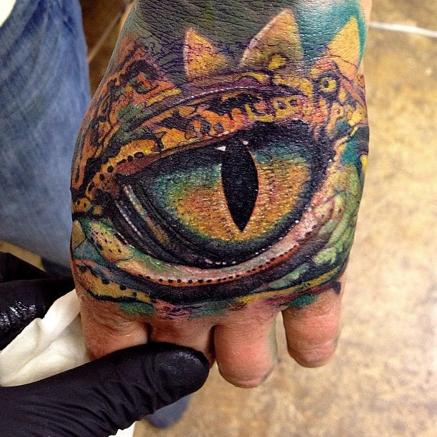 Realistic looking hand tattoo of dragon eye