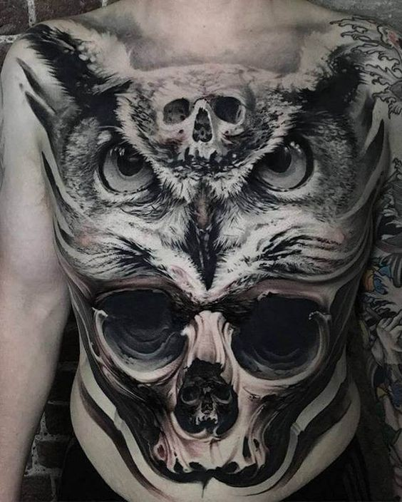 Realistic looking very detailed chest and belly tattoo of owl head with skulls