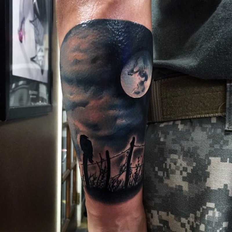 Realistic photo like colored crow on fence with moon tattoo on forearm