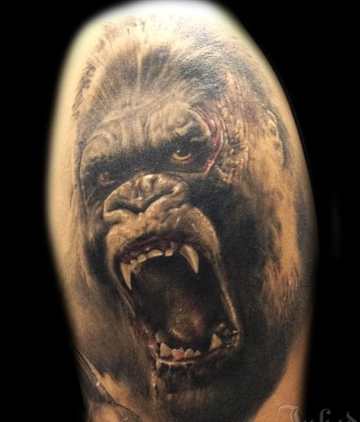 Realistic portrait of an angry gorilla tattoo on shoulder