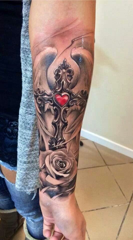 Realistic religious winged gray-ink cross with red heart and rose tattoo on forearm