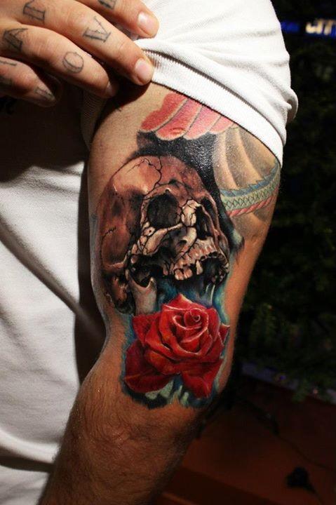 Tatuaje en el brazo, cráneo agrietado y rosa de color rojo brillante