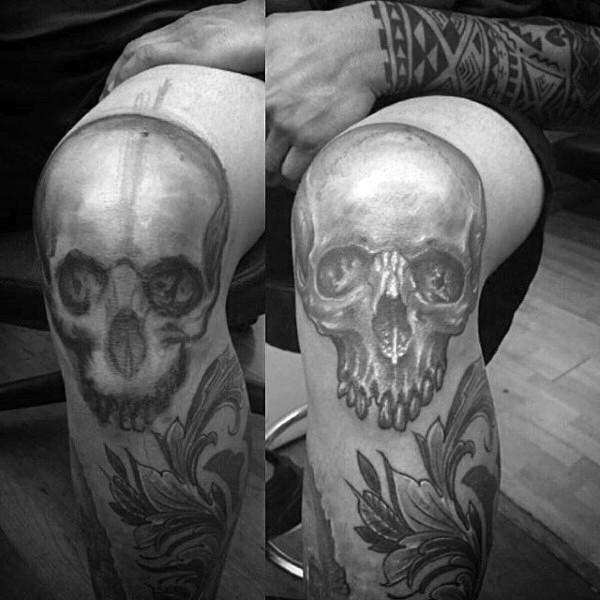 Realistic style black and white skull tattoo on knee