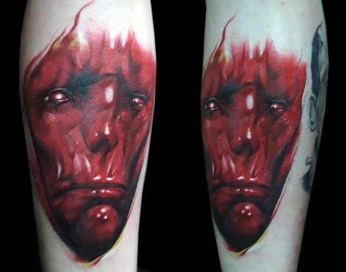 Red colored creepy looking arm tattoo of demonic face