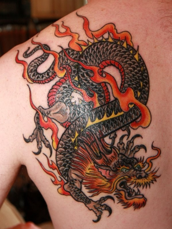Red dragon tattoo on shoulder blade