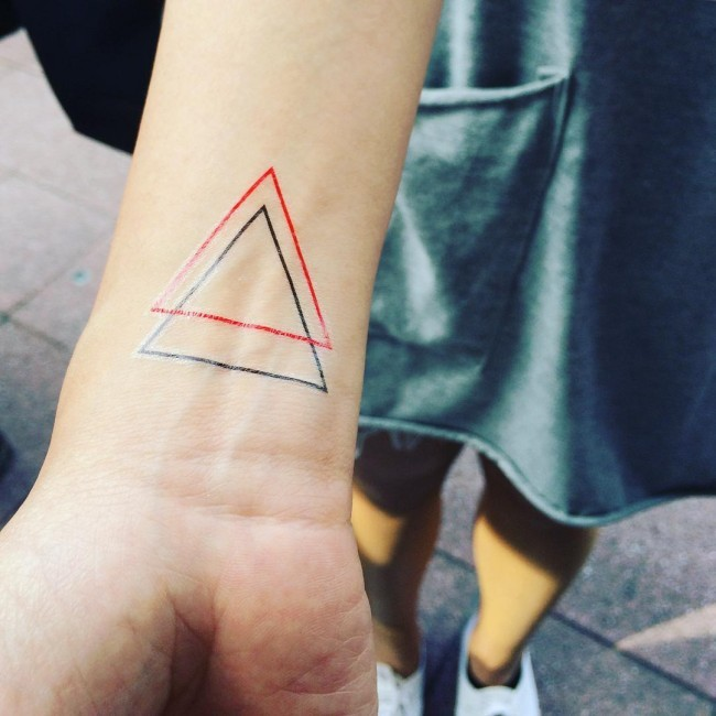 Red ink and black ink triangle thin line tattoo on wrist