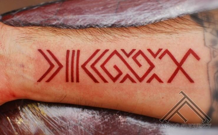 Red latin symbol forearm tattoo